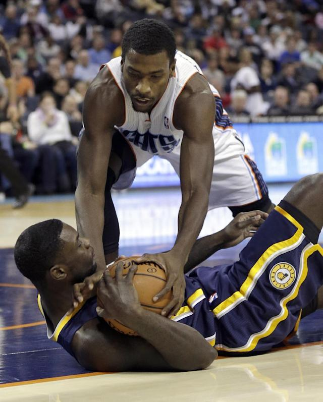 Charlotte Bobcats' Michael Kidd-Gilchrist, top, tries to steal the ball from Indiana Pacers' Lance Stephenson, bottom, during the first half of an NBA basketball game in Charlotte, N.C., Wednesday, Nov. 27, 2013. (AP Photo/Chuck Burton)