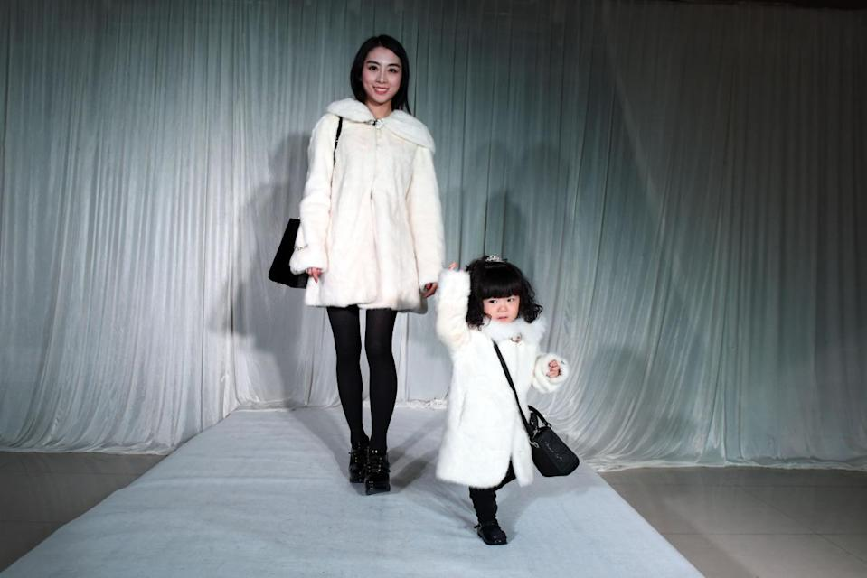 """Maybe a designer white fur coat is this mother's version of gifting her daughter a """"Frozen"""" costume."""