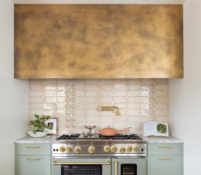 "<div class=""caption""> The backsplash tile was a collaboration with maker <a href=""https://www.yondershop.com/"" rel=""nofollow noopener"" target=""_blank"" data-ylk=""slk:Linda Fahey"" class=""link rapid-noclick-resp"">Linda Fahey</a>. ""I like geometric in general, and we took her dog bowl shape and made it a convex shape—playing with dimension—[and added] a rose-gold glaze,"" Regan says. </div> <cite class=""credit"">Photo: Suzanna Scott</cite>"