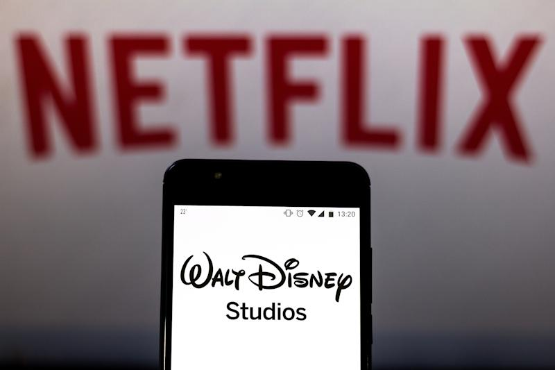 BRAZIL - 2019/08/16: In this photo illustration the Walt Disney Studios logo is seen displayed on a smartphone and logo Netflix on the blurred background. (Photo Illustration by Rafael Henrique/SOPA Images/LightRocket via Getty Images)