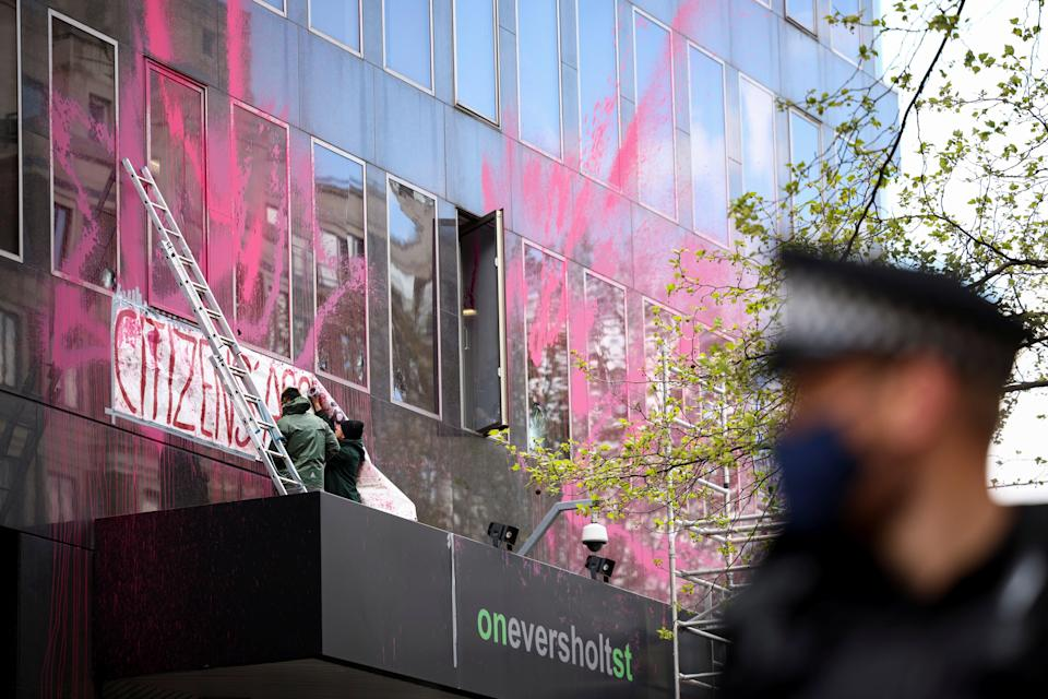 <p>Activists stretch a banner at the spray painted side of Euston station building to protest against the HS2 high-speed railway in London</p> (REUTERS)