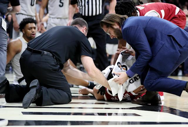 "Medical professionals tend to Oscar da Silva of the <a class=""link rapid-noclick-resp"" href=""/ncaaw/teams/stanford/"" data-ylk=""slk:Stanford Cardinal"">Stanford Cardinal</a> as he lays motionless on the court after fouling Evan Battey of the <a class=""link rapid-noclick-resp"" href=""/ncaaw/teams/colorado/"" data-ylk=""slk:Colorado Buffaloes"">Colorado Buffaloes</a> during the second half of their matchup on Saturday in Boulder. (Lizzy Barrett/Getty Images)"
