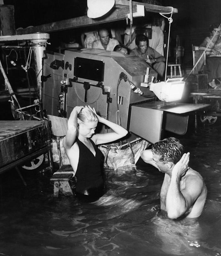 <p>Kelly is photographed with her costar, Cary Grant, in the water while filming <em>To Catch a Thief</em>. The heavy equipment used to film the actors in the ocean is seen behind them. </p>