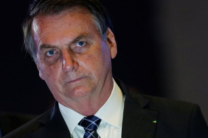 """Brazil's President Jair Bolsonaro looks on during the event """"Caixa Persons with disabilities"""" of Caixa Economica Federal Bank in Brasilia"""