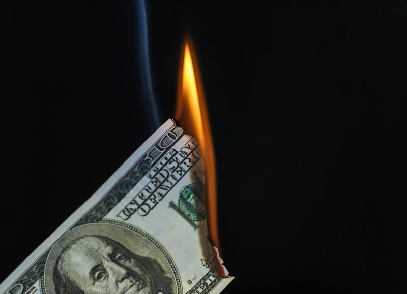 An image of a $100 bill burning.