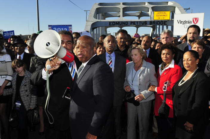 """FILE - In this March 4, 2012, file photo, U.S. Rep. John Lewis, D-Ga., center, talks with those gathered on the historic Edmund Pettus Bridge during the 19th annual reenactment of the """"Bloody Sunday"""" Selma to Montgomery civil rights march across the bridge in Selma, Ala. The March 7, 2021, Selma Bridge Crossing Jubilee will be the first without the towering presence of Lewis, as well as the Rev. Joseph Lowery, the Rev. C.T. Vivian and attorney Bruce Boynton, who all died in 2020. (AP Photo/Kevin Glackmeyer, File)"""