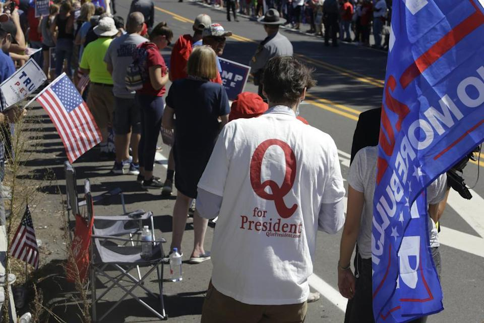 A man in a QAnon T-shirt walks among Trump supporters as they wait for Donald Trump to arrive and visit Mariotti Building Products in Old Forge, Pennsylvania, in August.