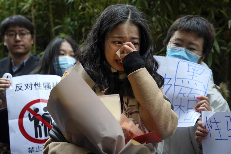 Zhou Xiaoxuan, center, weeps as she speaks to her supporters upon arrival at a courthouse in Beijing, Wednesday, Dec. 2, 2020. Zhou, a Chinese woman who filed a sexual harassment lawsuit against a TV host, told dozens of cheering supporters at a courthouse Wednesday she hopes her case will encourage other victims of gender violence in a system that gives them few options to pursue complaints. (AP Photo/Andy Wong)