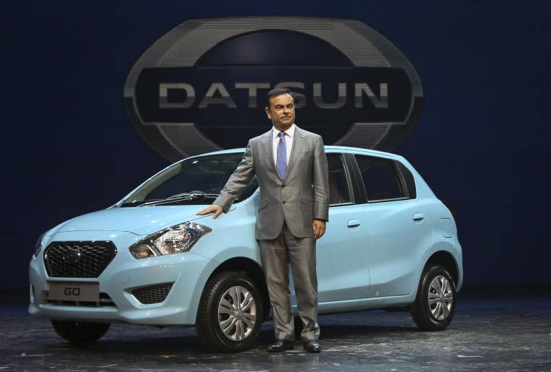 Nissan Motor Co. President and CEO Carlos Ghosn poses for the media with Datsun Go during its global launch in New Delhi, India, Monday, July 15, 2013. Nissan has introduced the first new Datsun model in more than three decades in the Indian capital. The company hopes bringing back the brand that built its U.S. business will fuel growth in emerging markets with a new generation of car buyers. The reimagined Datsun - a five-seat hatchback - will go on sale in India next year for under 400,000 rupees (about $6,670). (AP Photo/Manish Swarup)