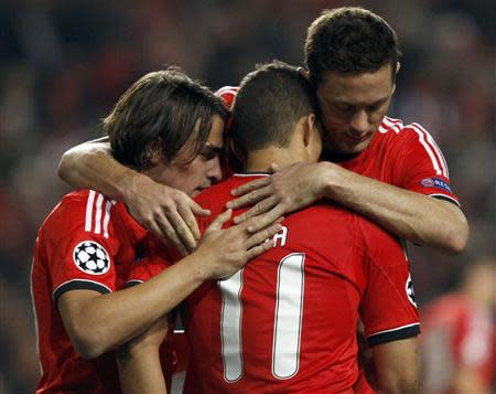 Benfica's Lima is congratulated by team mates after scoring a penalty against Paris St Germain during their Champions League soccer match in Lisbon