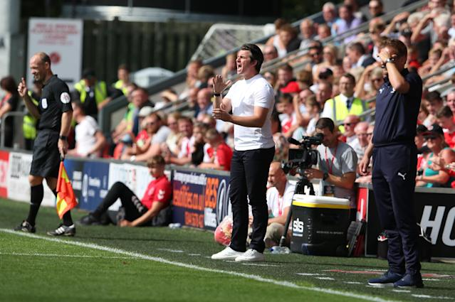 Cameras can be seen documenting Joey Barton on the touchline during his managerial debut