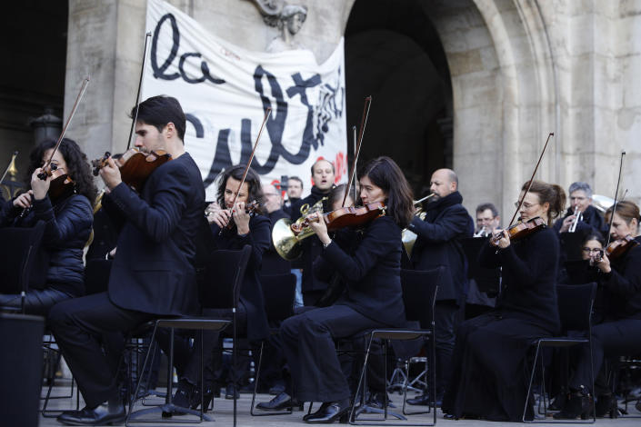 Striking musicians perform outside the Palais Garnier opera house, Saturday, Jan. 18, 2020 in Paris. As some strikers return to work, with notable improvements for train services that have been severely disrupted for weeks, more radical protesters are trying to keep the movement going. (AP Photo/Kamil Zihnioglu)