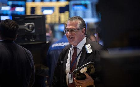 Trader Kenneth Polcari smiles as he works on the floor of the New York Stock Exchange at the market opening in New York, December 23, 2013. REUTERS/Carlo Allegri