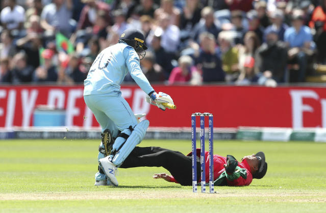 England's Jason Roy collides with the umpire Joel Wilson after hitting his century during the ICC Cricket World Cup group stage match between England and Bangladesh at the Cardiff Wales Stadium, Wales, Saturday, June 8, 2019. (David Davies/PA via AP)