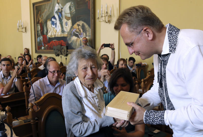 Lviv Mayor Andriy Sadoviy, right, presents a glass copy of an old metal synagogue key to Yanina Hescheles, Polish writer and a Nazi concentration camp survivor, at a ceremony commemorating the 75th anniversary of the annihilation of the city's Jewish population by Nazi Germany in Lviv, Ukraine, Sunday, Sept. 2, 2018. The Ukrainian city of Lviv, once a major center of Jewish life in Eastern Europe, is commemorating the 75th anniversary of the annihilation of the city's Jewish population by Nazi Germany and honoring those working today to preserve that vanished world. The commemoration comes amid a larger attempt in Ukraine to preserve the memories of the prewar Jewish community. (AP Photo/Yevheniy Kravs)