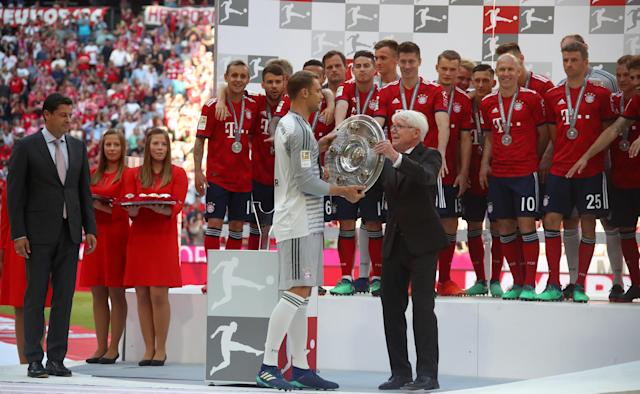 Soccer Football - Bundesliga - Bayern Munich v VfB Stuttgart - Allianz Arena, Munich, Germany - May 12, 2018 Bayern Munich's Manuel Neuer receives the trophy while team mates look on as they celebrate winning the Bundesliga REUTERS/Michael Dalder DFL RULES TO LIMIT THE ONLINE USAGE DURING MATCH TIME TO 15 PICTURES PER GAME. IMAGE SEQUENCES TO SIMULATE VIDEO IS NOT ALLOWED AT ANY TIME. FOR FURTHER QUERIES PLEASE CONTACT DFL DIRECTLY AT + 49 69 650050