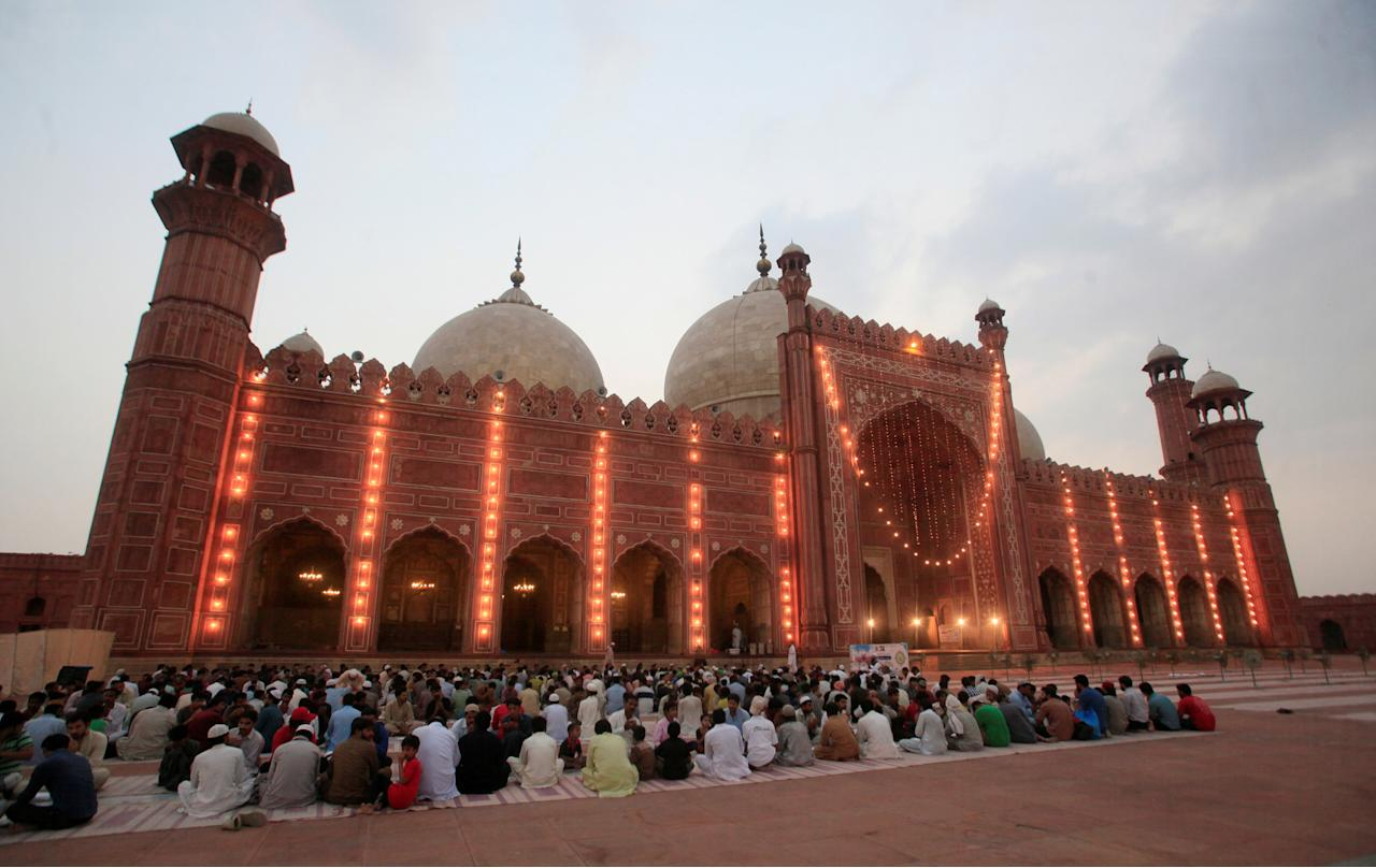 People sit before breaking their fast at the lawns of the Badshahi Mosque during the Muslim holy month of Ramadan in Lahore, Pakistan, June 22, 2017. REUTERS/Mohsin Raza