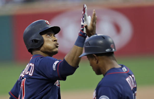Minnesota Twins' Jorge Polanco, left, is congratulated by third base coach Tony Diaz after hitting a two-run home run in the first inning in a baseball game against the Cleveland Indians, Friday, Sept. 13, 2019, in Cleveland. (AP Photo/Tony Dejak)
