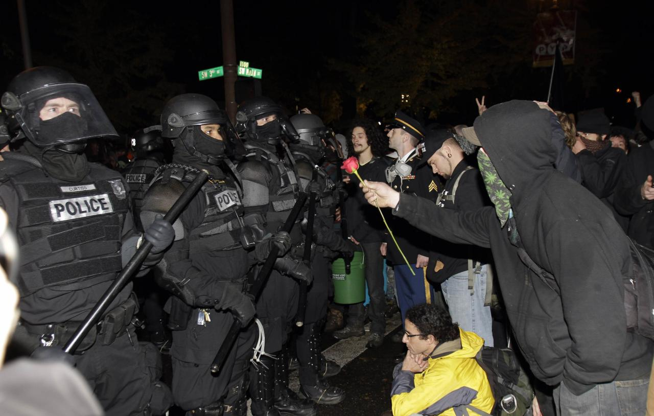 A protester offers police a rose after the deadline passed when the city wanted them to vacate the Occupy Portland Camp in Portland, Ore., Sunday, Nov. 13, 2011. Thousands of protesters showed up as mounted police and police in riot gear moved in but were forced to back down by the crowd. (AP Photo/Don Ryan)