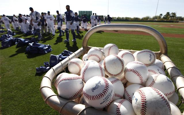 Baseballs rest in a basket as the Los Angeles Dodgers head to drills during spring training baseball practice in Glendale, Ariz., Friday, Feb. 14, 2014