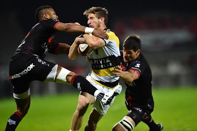 La Rochelle's Vincent Rattez (C) vies with Lyon's Julien Puricelli (R) during their French Top 14 rugby union match on April 15, 2017 at the Matmut stadium in Lyon, central eastern France (AFP Photo/ROMAIN LAFABREGUE)