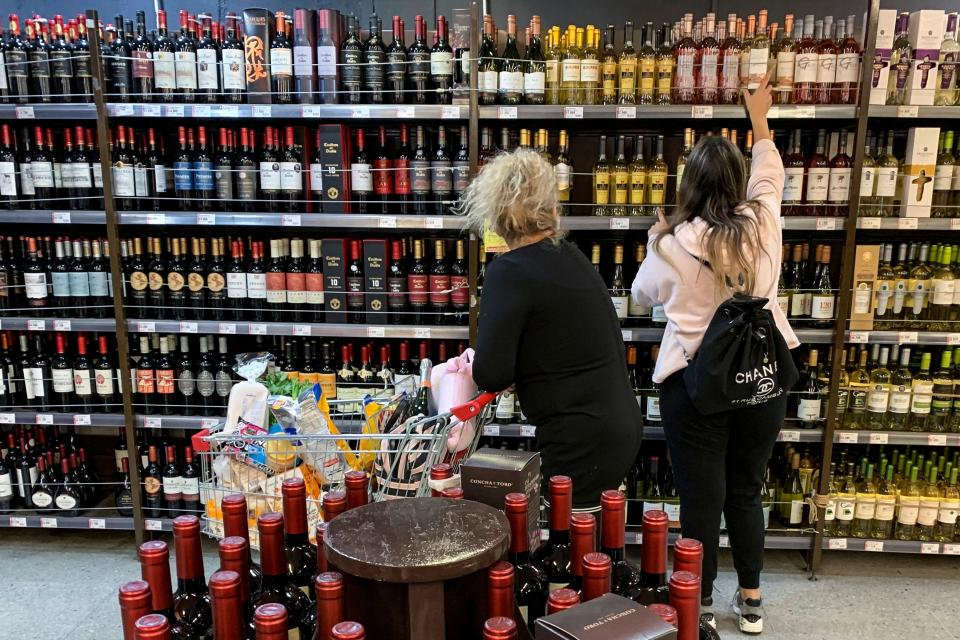 A woman reaches for a bottle of wine in a supermarket. Photo: Martin Bernetti/AFP via Getty