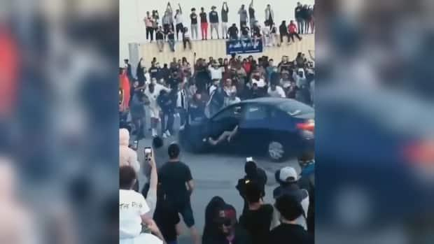Hundreds of people turned out to a car meet in Pickering, Ont., Sunday, where at least onecar performed stunts, doing doughnuts with the front doors open as a cluster of onlookers cheered. (@6ixbuzz_ent/Instagram - image credit)