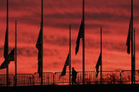 A solitary runner passes under the flags hanging at half-staff surrounding the Washington Monument at day break in Washington, Wednesday, Feb. 24, 2021. President Joe Biden ordered the flags to be lowered in honor of the 500,000 lives lost to COVID-19 in the U.S. (AP Photo/J. David Ake)