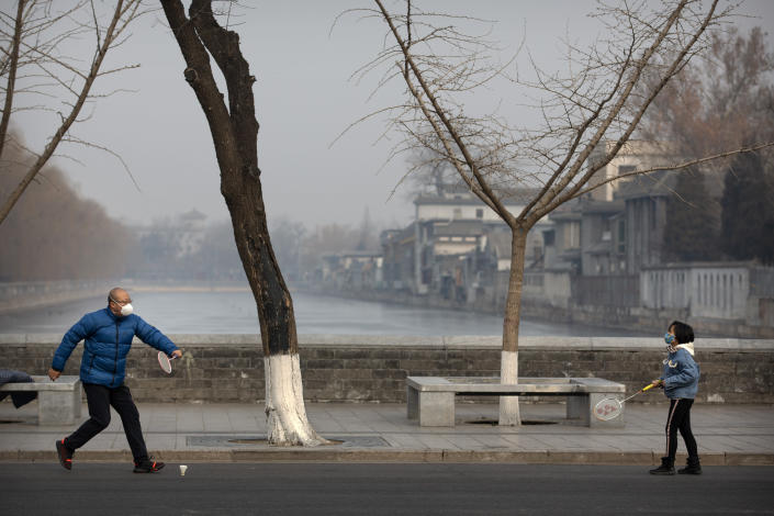 A man and girl wear face masks as they play badminton near the closed Forbidden City in Beijing, Monday, Jan. 27, 2020. China on Monday expanded sweeping efforts to contain a viral disease by postponing the end of this week's Lunar New Year holiday to keep the public at home and avoid spreading infection. (AP Photo/Mark Schiefelbein)