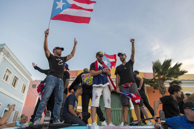 Singer Ricky Martin, left, waves the Puerto Rican flag during march against governor Ricardo Rosello, in San Juan, Puerto Rico, July 17, 2019. Protesters are demanding Rossello step down for his involvement in a private chat in which he used profanities to describe an ex-New York City councilwoman and a federal control board overseeing the island's finance. (Photo: Dennis M. Rivera Pichardo/AP)