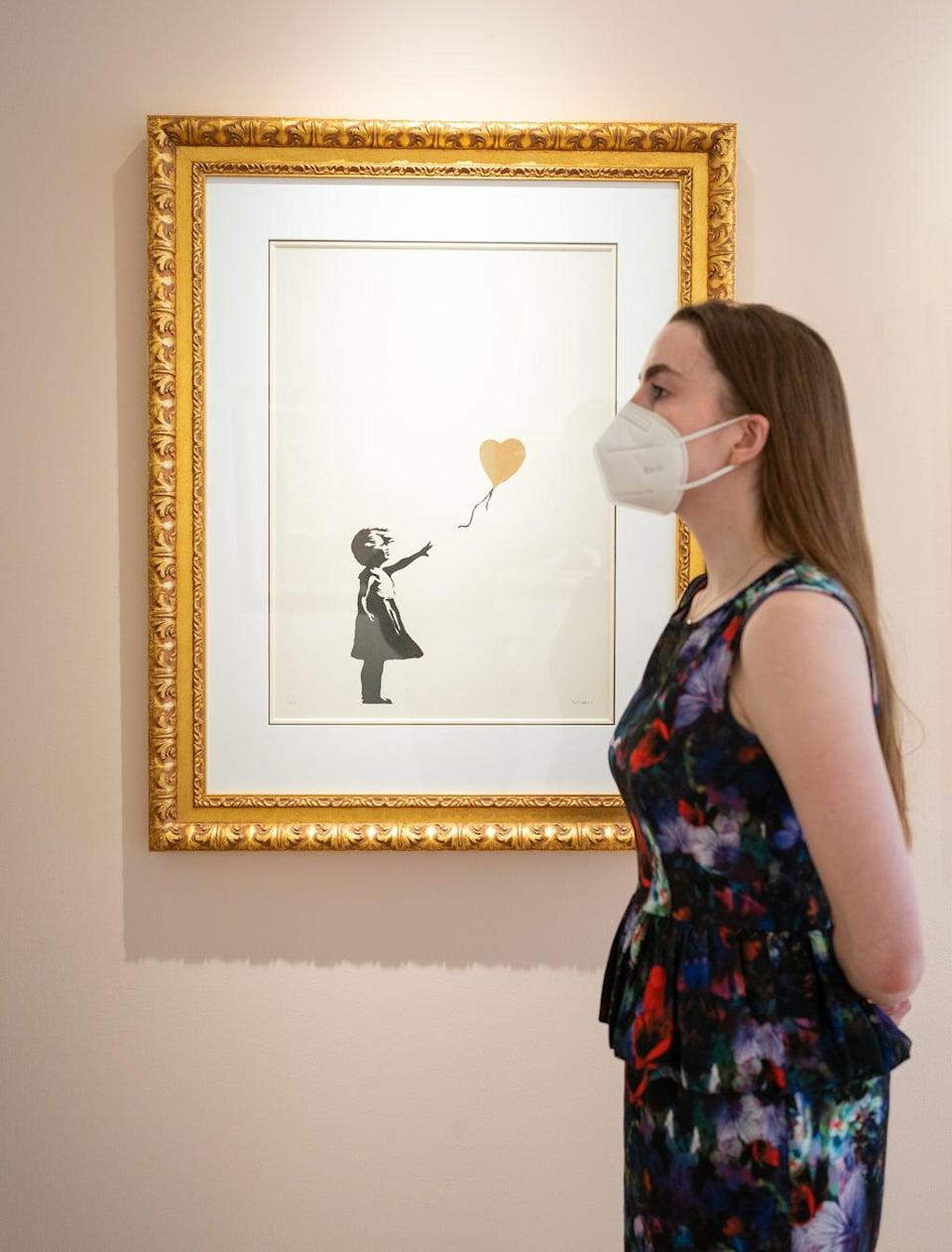 Rare works from subversive street artist Banksy – including Girl With Balloon – Colour AP (gold) – went on display ahead of an auction later this month (Dominic Lipinski/PA) (PA Wire)