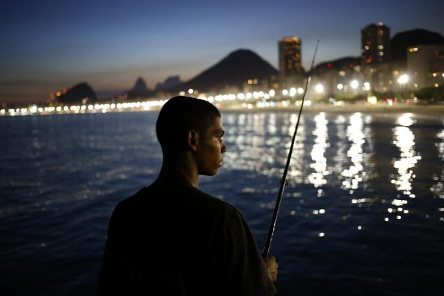 A fisherman waits for a catch in front of the beach of Copacabana in Rio de Janeiro, March 18, 2014. REUTERS/Jorge Silva (BRAZIL - Tags: SOCIETY TPX IMAGES OF THE DAY)
