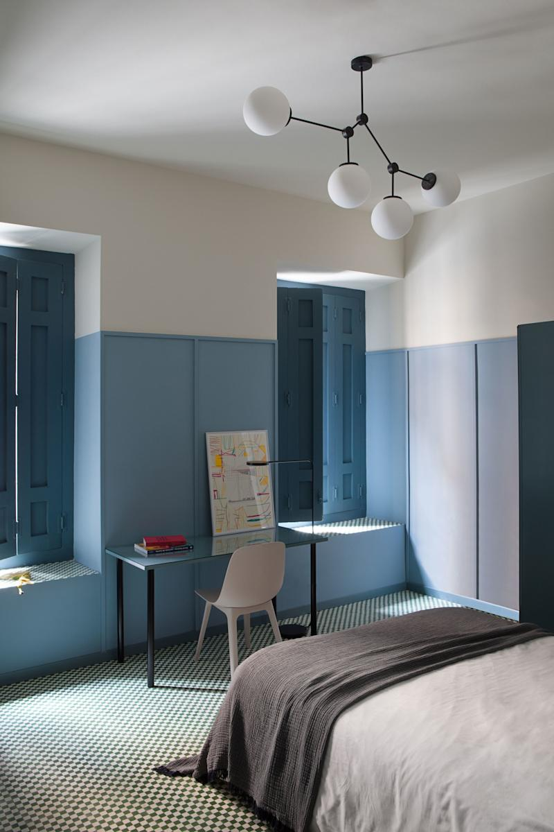 """After: Ana and Enrique warmed up the space, now called the """"Blue and Green Room,"""" with wall paneling in a robin's egg blue. The matching desk is actually IKEA legs paired with a custom table top."""