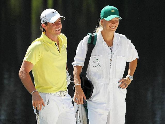 "FILE - In this April 10, 2013, file photo, Rory McIlroy, left, of Northern Ireland, and his caddie, tennis player Caroline Wozniacki, share a laugh on the fourth hole during the par-3 competition at the Masters golf tournament in Augusta, Ga. One of the top power couples in sports announced their engagement on Twitter. A spokesman for McIlroy confirmed that he popped the question in Sydney, where Wozniacki is starting to prepare for the Australian Open in Melbourne. McIlroy tweeted, ""Happy New Year everyone! I have a feeling it's going to be a great year!! My first victory of 2014."" He added a hash tag, ""She said yes!!"" (AP Photo/Atlanta Journal-Constitution, Curtis Compton, File)"