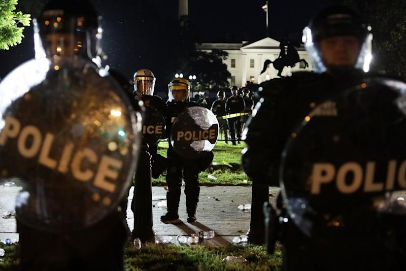Members of the US Secret Service hold a perimeter near the White House as demonstrators gather to protest the killing of George Floyd on Saturday in Washington DC.