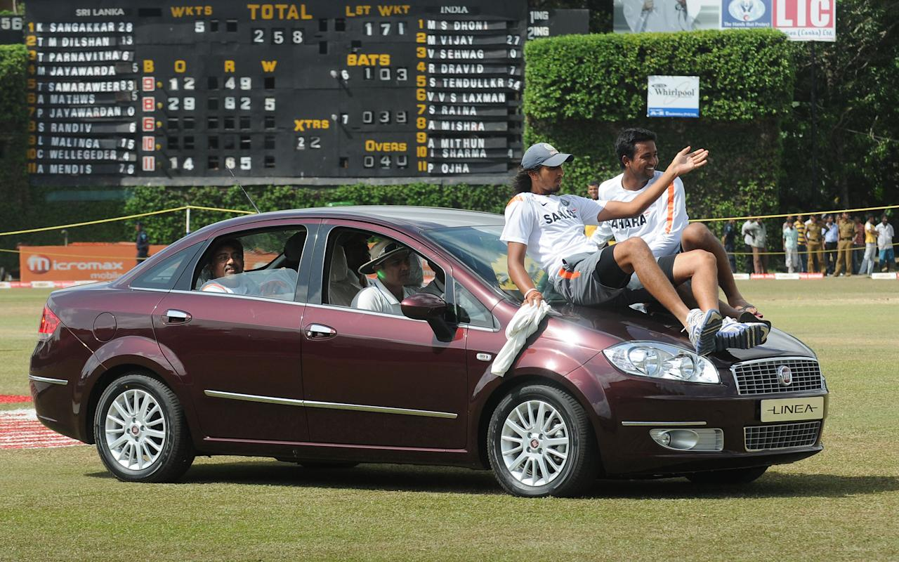 Indian cricketer Virender Sehwag, seen in the driver's seat, gives his teammates a ride in a car presented to him after receiving the Man of The Series trophy following the third Test match between Sri Lanka and India at The P. Sara Oval International Cricket Stadium in Colombo on August  7, 2010. Venkatsai Laxman overcame back spasms to hit an unbeaten 103 as India defeated Sri Lanka by five wickets in the final Test to draw the three-match series 1-1. AFP PHOTO/Lakruwan WANNIARACHCHI