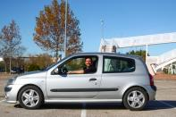 Cristian Lopez poses with his newly-bought 15-year-old second hand car in an empty parking lot in Madrid