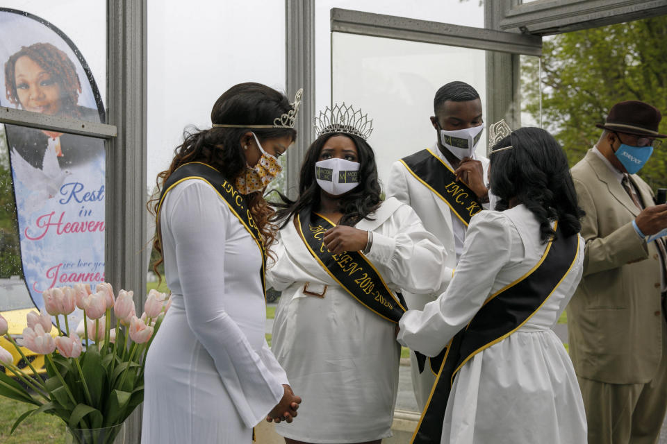 """Models Inc. Queens including Jewel Parker, left, and Goldie Demetria, center, with Cougar Francis, a Models Inc. King, at right, adjust their sashes and tiaras as they arrive for the viewing of Joanne Paylor, 62, of southwest Washington, at Cedar Hill Cemetery in Suitland-Silver Hill, Md., Sunday, May 3, 2020. Models Inc. is a community organization founded Paylor's son, Iran """"Bang"""" Paylor, that was supported by his mother. Despite not having died from coronavirus, almost every aspect of her funeral has been impacted by the pandemic. (AP Photo/Jacquelyn Martin)"""