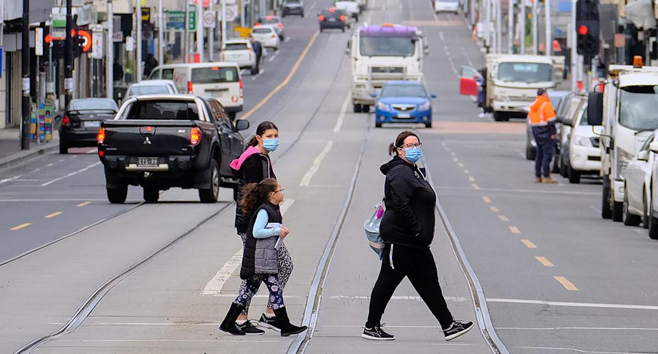 A woman and two children wearing face masks walking across the road in Melbourne.