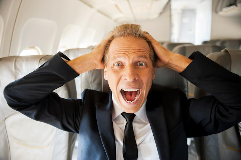 Shocked mature businessman touching his head with hands and looking at camera while sitting at his seat in airplane