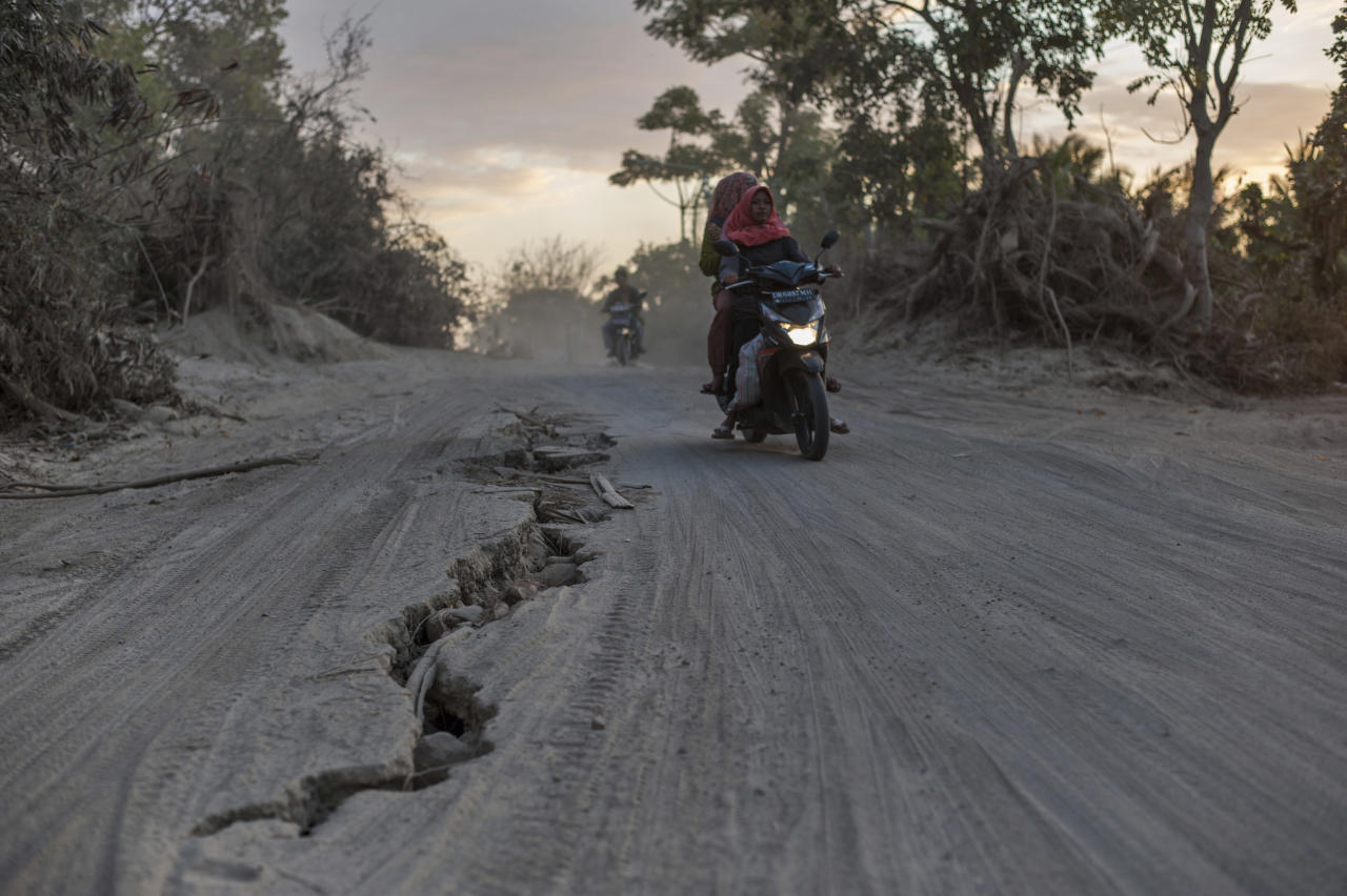 <p>Motorists ride past a road torn apart by Sunday's earthquake in Gangga, Lombok Island, Indonesia, Saturday, Aug. 11, 2018. (Photo: Fauzy Chaniago/AP) </p>