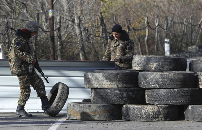 Ethnic Armenian militants stand at a checkpoint near village of Charektar in the separatist region of Nagorno-Karabakh at a new border with Kalbajar district turned over to Azerbaijan, Wednesday, Nov. 25, 2020. The Azerbaijani army has entered the Kalbajar region, one more territory ceded by Armenian forces in a truce that ended deadly fighting over the separatist territory of Nagorno-Karabakh, Azerbaijan's Defense Ministry said Wednesday. The cease-fire, brokered by Russia two weeks ago, stipulated that Armenia hand over control to Azerbaijan of some areas its holds outside Nagorno-Karabakh's borders. (AP Photo/Sergei Grits)