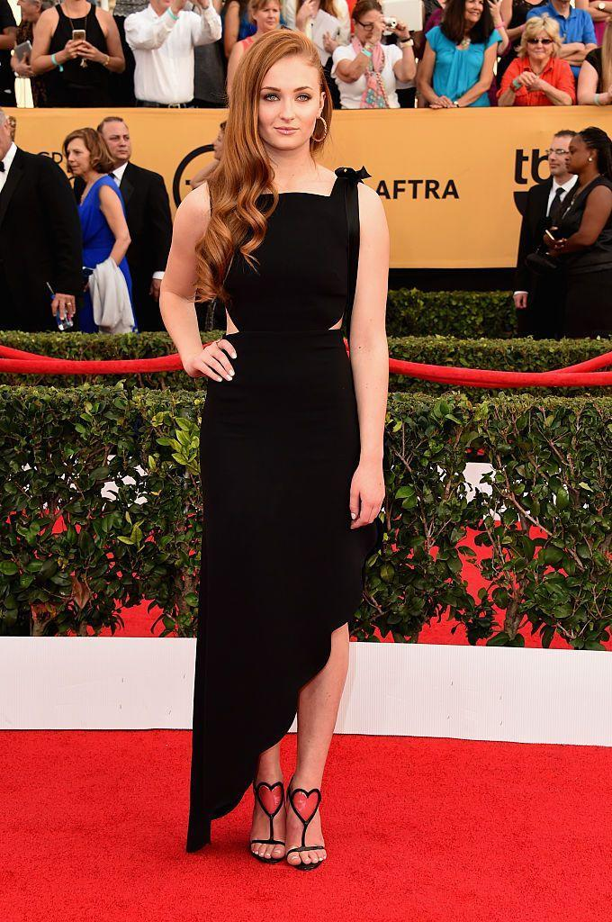 <p>Turner wore an asymmetric black midi dress by Osman and Christian Louboutin shoes.</p>