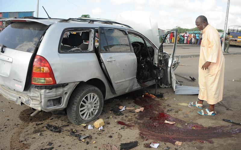 A Somali man stands near a vehicle after a car bomb exploded, killing at least one person and injuring several others Mogadishu on November 1, 2014