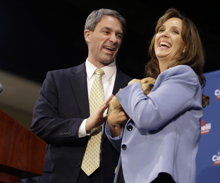 Republican gubernatorial candidate, Virginia Attorney General Ken Cuccinelli, left, smiles along with his wife, Teiro, as she holds a puppy during a rally at Republican headquarters in Richmond, Va., Monday, Nov. 4, 2013. Cuccinelli faces Democrat Terry McAuliffe in Tuesday's election. (AP Photo/Steve Helber)
