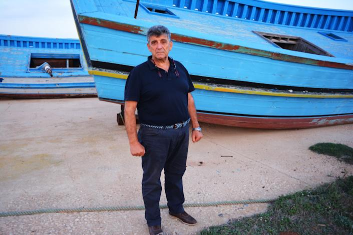 Dr Pietro Bartolo stands in front of a dilapidated migrant boat one of the many on show on a patch of shrubland in Lampedusa