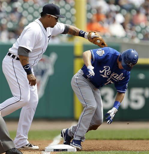 Kansas City Royals' Chris Getz avoids the tag of Detroit Tigers third baseman Miguel Cabrera on a triple in the second inning of a baseball game in Detroit, Wednesday, May 2, 2012. (AP Photo/Paul Sancya)