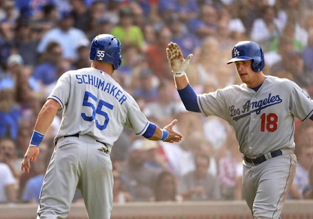 Los Angeles Dodgers' Tim Federowicz high-fives Skip Schumaker (55) after they scored on an RBI single hit by teammate Carl Crawford during the sixth inning of a baseball game against the Chicago Cubs, Saturday, Aug. 3, 2013, in Chicago. (AP Photo/Brian Kersey)