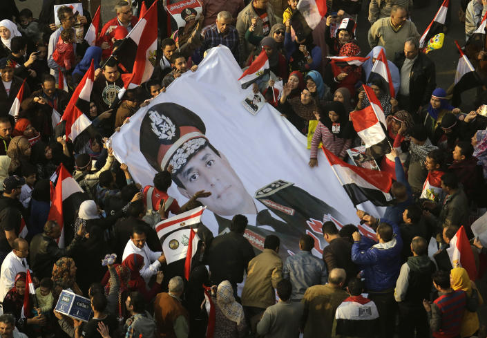FILE - In this Saturday, Jan. 25, 2014 file photo, Egyptians wave a giant poster of Egypt's Defense Minister, Gen. Abdel-Fattah el-Sissi in Tahrir Square, the epicenter of the 2011 uprising, in Cairo, Egypt. The head of Egypt's military, Abdel-Fattah el-Sissi, is riding on a wave of popular fervor that is almost certain to carry him to election as president. Unknown only two years ago, a broad sector of Egyptians now hail him as the nation's savior after he ousted the Islamists from power, and the state-backed personality cult around him is so eclipsing, it may be difficult to find a candidate to oppose him if he runs. Still, if he becomes president, he faces the tough job of ruling a deeply divided nation that has already turned against two leaders. (AP Photo/Amr Nabil, File)