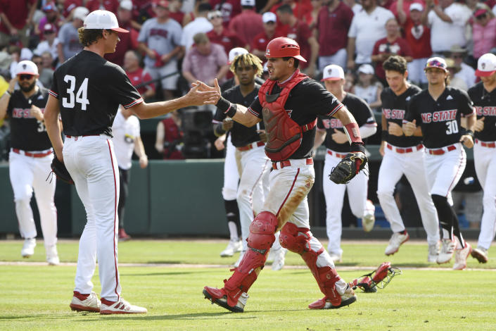 North Carolina State pitcher Evan Justice (34) celebrates with catcher Luca Tresh, front right, after defeating Arkansas in an NCAA college baseball super regional game Saturday, June 12, 2021, in Fayetteville, Ark. (AP Photo/Michael Woods)